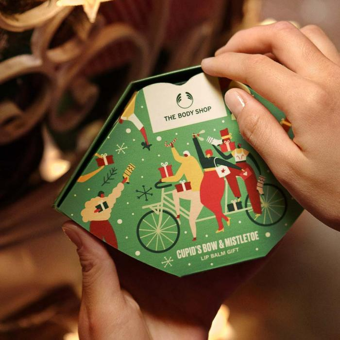 Hand holding a green  gift box of lip balms