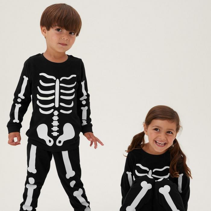 Two children wearing black and white skeleton pyjamas