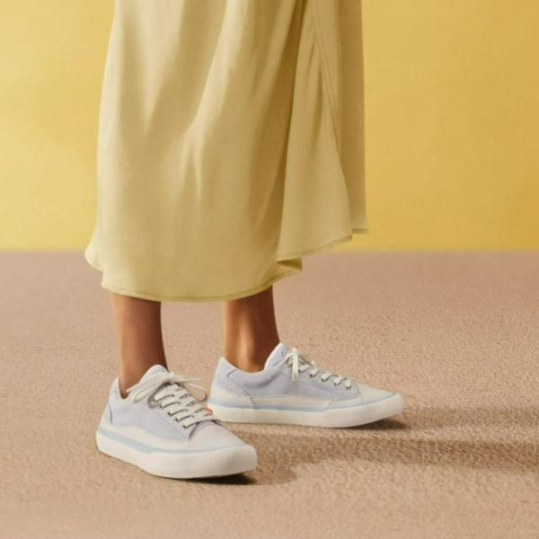 Model wearing long yellow dress and pale blue Clarks trainers